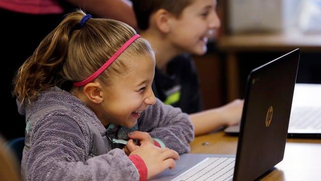 Mädchen in der Schule am Laptop, lacht sich weg