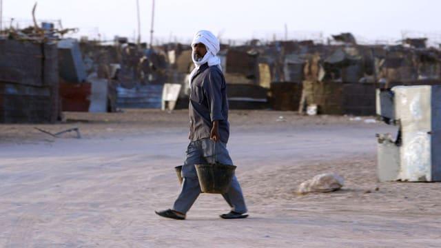 Ein Mann mit Turban schleppt Wassereimer durch eine Strasse mit zerfallenen Hütten.