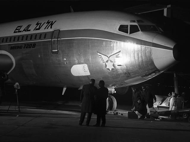 Fotografen machen Fotos eines stehenden Flugzeuges mit Einschusslöchern