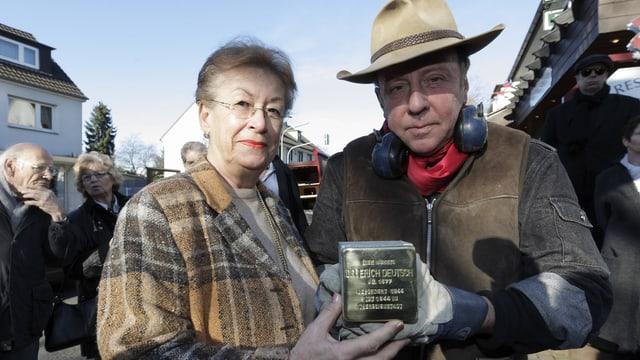 Deming und eine Frau halten einen Stolperstein in die Kamera