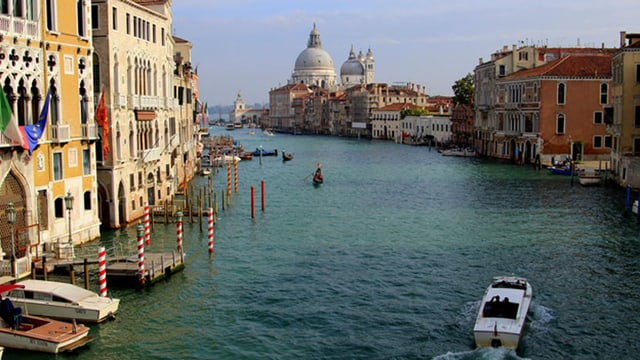 Ein sonniger Tag in Venedig. Ein Boot fährt durch den Kanal.