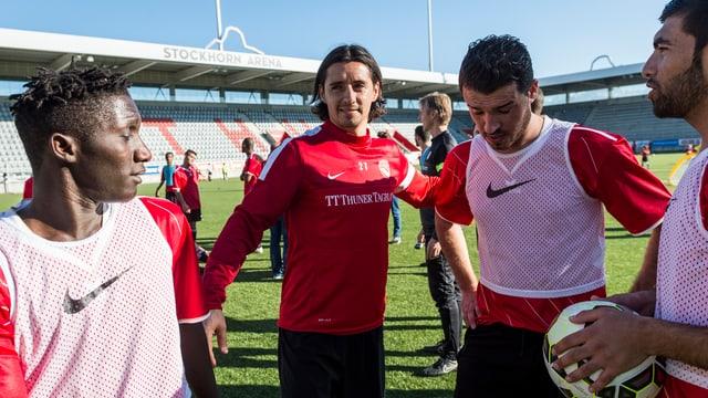 Thun-Spieler Nelson Fereirra zusammen mit Flüchtlingen in der Stockhorn Arena.