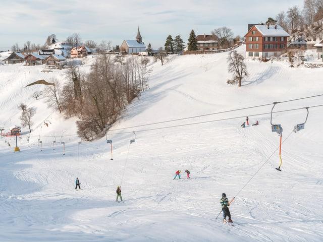 Blick auf Sternenberg im Schnee. Auf dem Skilift fahren mehrere Kinder.