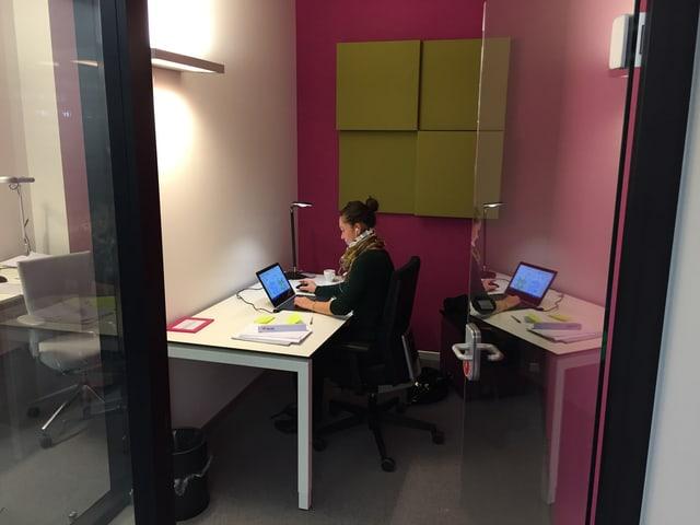 Glasbox mit einem Schreibtisch, eine junge Frau arbeitet an einem Laptop