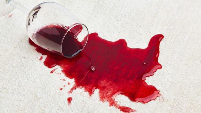 Ausgeschüttetes Rotweinglas auf einem weissen Teppich.