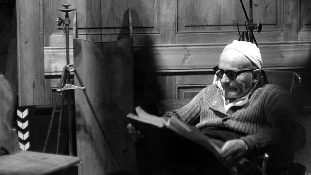 Ein älterer Mann sitzt auf einem Regiestuhl und liest im Drehbuch.