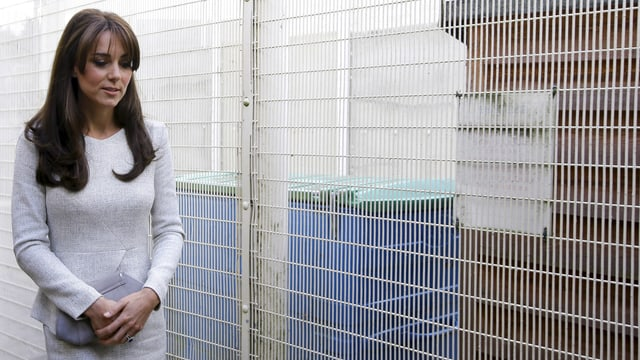 Kate in einem grauen Business-Outfit läuft mit gesenktem Kopf einem Gitter entlang.