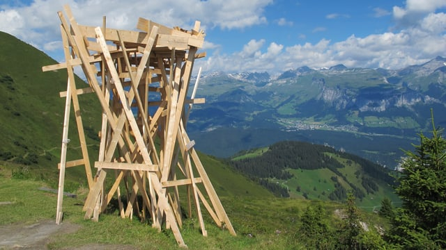 Ein Holzgerüst, das an einen Turm erinnert inmitten einer alpinen Sommerlandschaft.