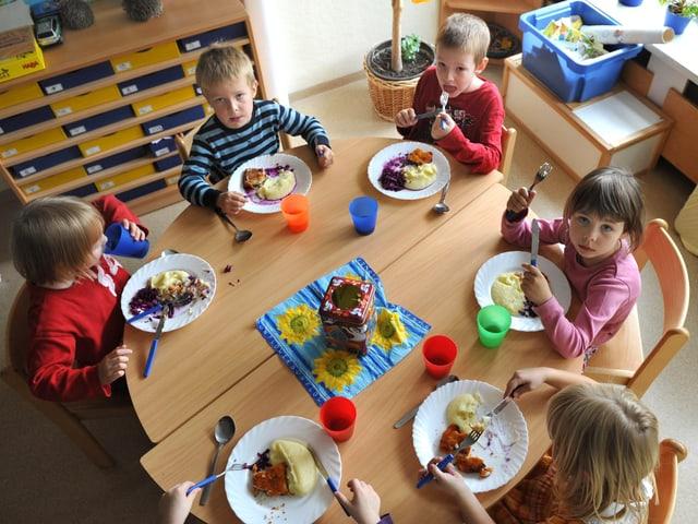 Kinder sitzen an einem runden Tisch und essen.