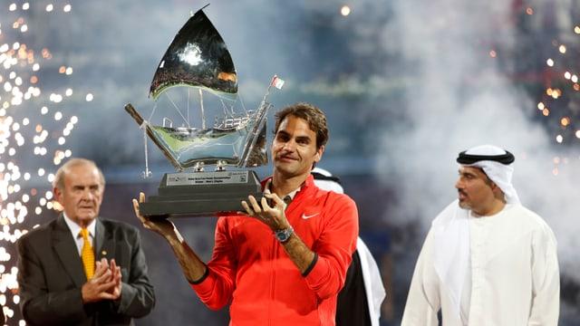 Roger Federer präsentiert auf dem Court in Dubai die Siegestrophäe.