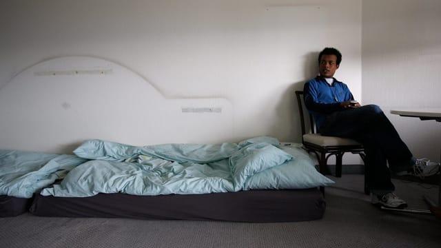Ein schwarzer Mann sitzt auf einem Stuhl neben einer Matratze.