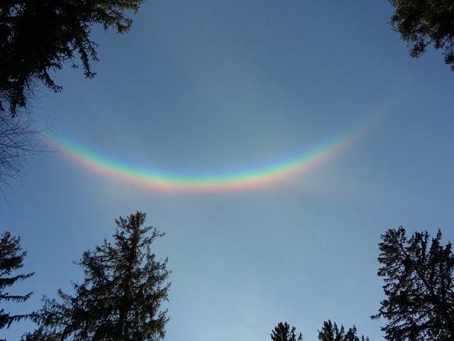 Blauer Himmel mit einem Regenbogen, der auf dem Kopf steht.