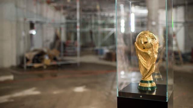 Die goldene WM-Trophäe vor dem Hintergrund von Baugerüsten.