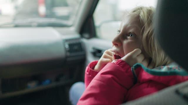 Ein Mädchen sitzt auf dem Beifahrersitz eines Autos und schreit
