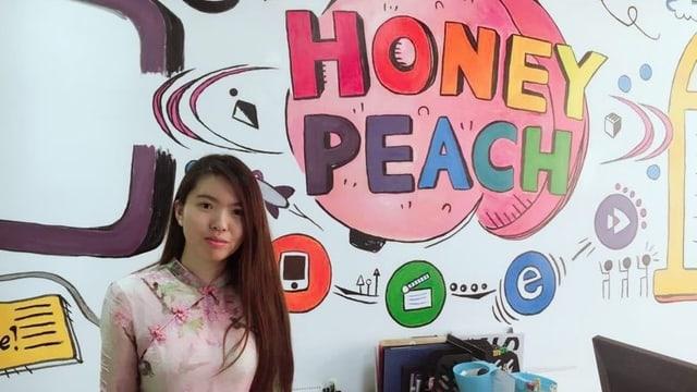 Die Chinesin Wang Yilin steht vor einem Logo ihrer Firma «Honey Peach».
