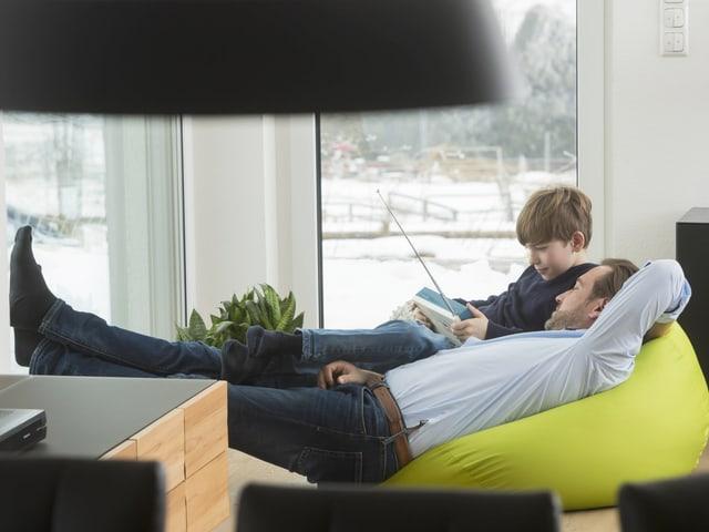 Ein Mann und ein Junge liegen auf einem Sitzsack in einem Wohnzimmer. SIe schauen lächelnd auf ein Radiogerät, das der Junge in der Hand hält.