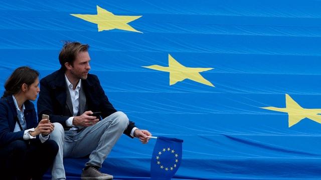 Menschen sitzen auf EU-Flagge.