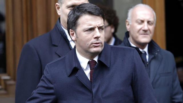 Renzi mit grimmigem Gesicht in blauem Mantel, hinter ihm zwei Männer, ebenfalls in blauen Mänteln.