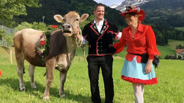 Eine Frau und ein Mann stehen neben einer Kuh, im Hintergrund die Berge.