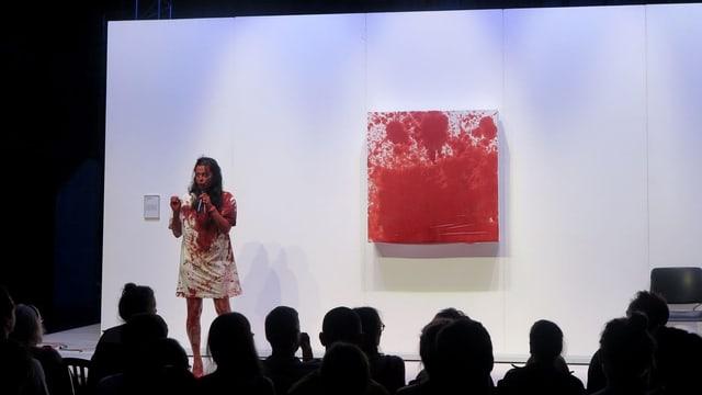 Eine Frau auf einer Bühne in einem blutverschmierten Kleid steht neben einem blutroten Bild.