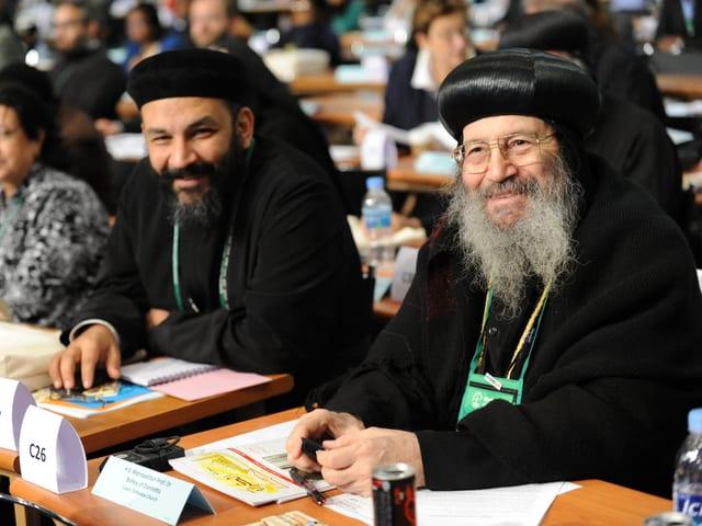 Zwei Männer mit Bart und schwarzen Hüten sitzen lächelnd an einem Tisch.