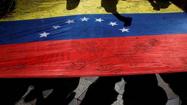 Eine venezolanische Flagge am Boden mit Kritzeleien darauf.