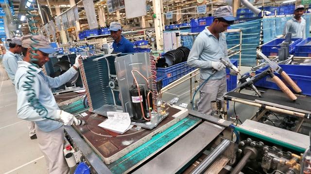 Arbeiter in einer indischen Farbik setzen Klimageräte zusammen.
