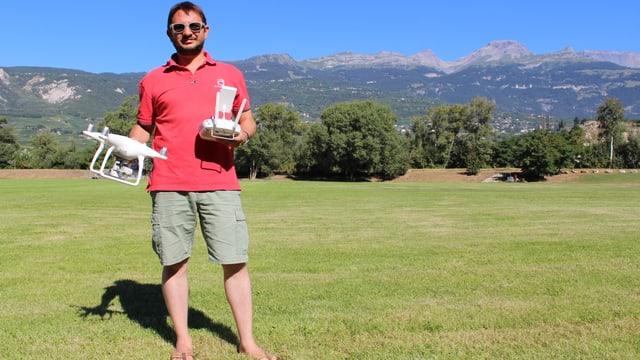 Frédéric Hemmeler steht mit einer Drohne in der Hand auf einem Rasen.