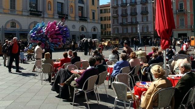 Menschen auf einer Piazza, Getränke auf den Tischen