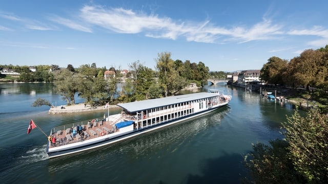 Ein Schiff fährt an der Rheininsel bei Rheinfelden vorbei.