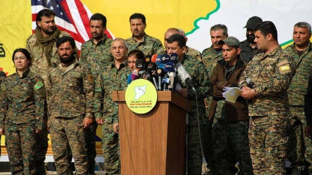 Mazlum Abdi umgeben von Militär-Angehörigen am Rednerpult.