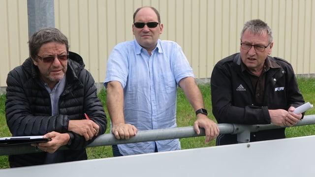 Drei Herren schauen auf ein Spielfeld.
