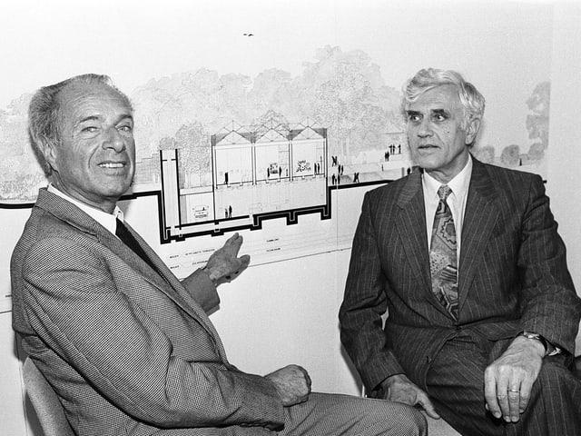 Archivbild: Zwei Männer im Anzug sitzen vor einer Bau-Skizze der Fondation.