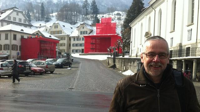En Mann vor dem Stanser Dorfplatz mit rot eingefassten Bühnen.