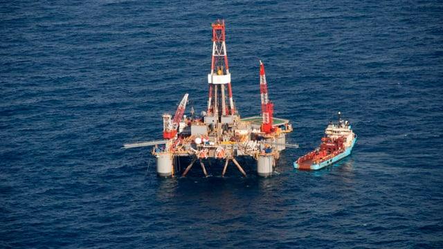 Eine Ölplattform schwimmt auf dem Meer begleitet von einem Schiff.