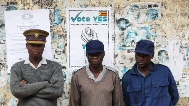 Drei Polizisten vor einem Wahlplakat, das für das Verfassungsreferendum wirbt.