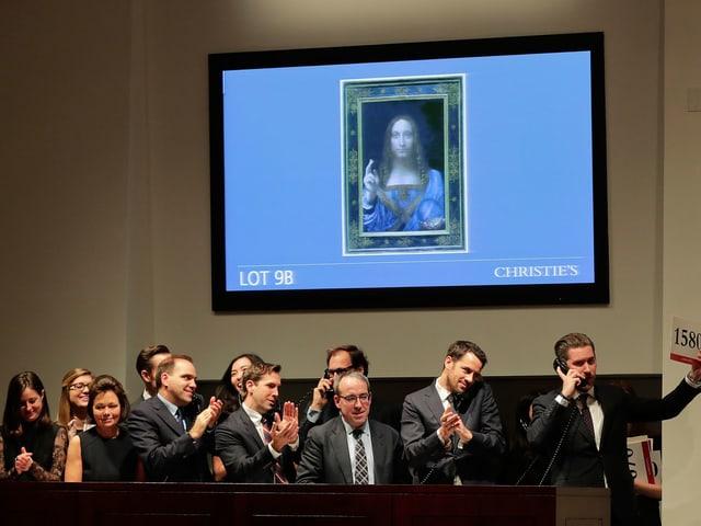 Leute applaudieren unter einem projizierten Bild von da Vinci
