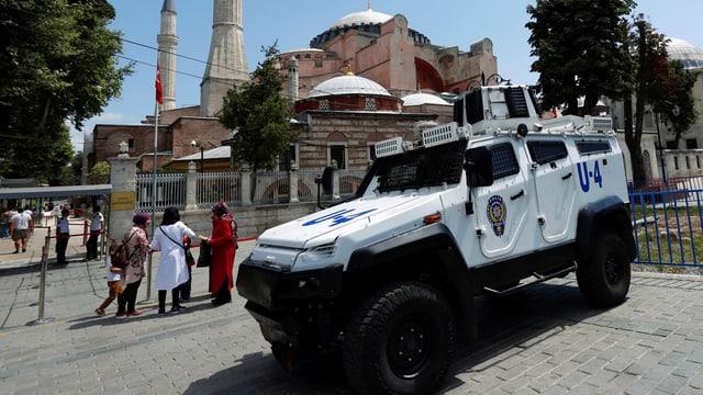 In jeep armà da la polizia tirca sin ina plazza avant la Hagia Sophia ad istanbul. Ins vesa dus minarets e persunas che stattan davos il char armà.