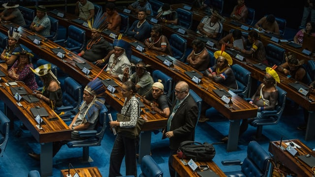 Indigene mit Federschmuck auf dem Kopf sitzen in einem Kongress.
