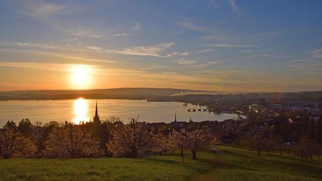 Die Sonne geht über einem See unter.