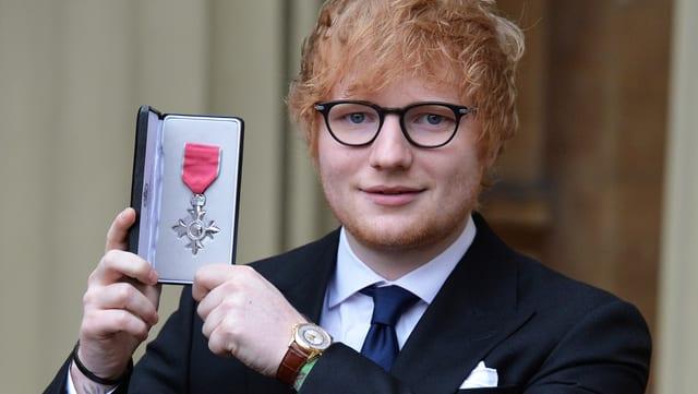Ed Sheeran hält seinen Orden in den Händen.