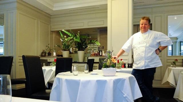 Ein stämmiger Mann in weisser Kochschürze steht an einem Tisch mit weissem Tischtuch und schwarzen Stühlen und schaut in die Kamera.