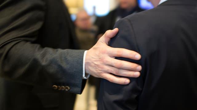 Geschäftsmänner: Einer legt Hand auf Schulter des anderen.