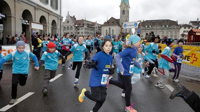 Kinder in hellblauen Kappen und blauen Pullovern rennen über eine Strasse, dahinter das Zürcher Fraumünster.