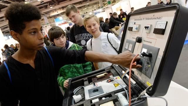 Jugendliche an einem elektrischen Gerät, einer schraubt daran herum, die anderen schauen zu.