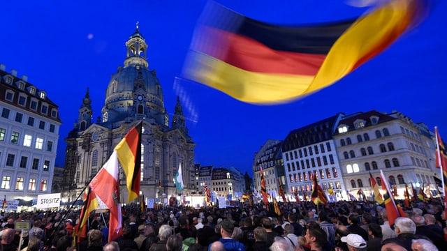 Hunderte Menschen, im Hintergrund Häuser, eine Deutschland-Fahne.