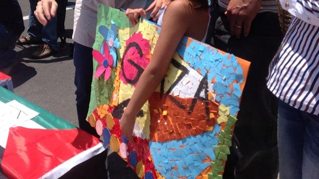 Ein Mädchen hält ein gemaltes Plakat mit der Auffschrift «Gaza» unter dem Arm.