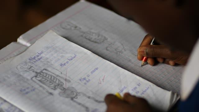 ein Kind schreibt in ein Schulbuch in seiner Muttersprache