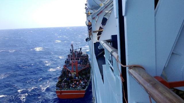 Kleines Boot, daneben Schiff. Leute im Boot.