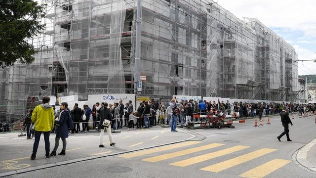 Hunderte Menschen stehen Schlange, um neue Wohungen in der Nähe des Bucheggplatzes in Zürich besichtigen zu können.